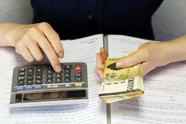お金を持ちながら電卓で計算