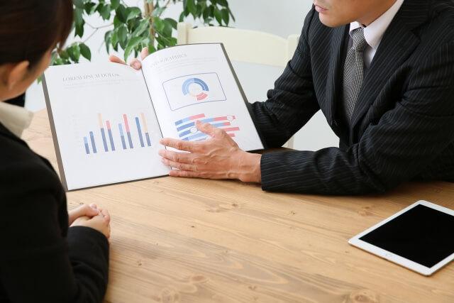 業者にデータを見せてもらう女性